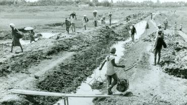 Laborers repairing a small secondary canal